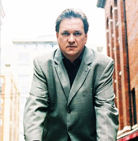 Portrait of man in suit with buildings behind him