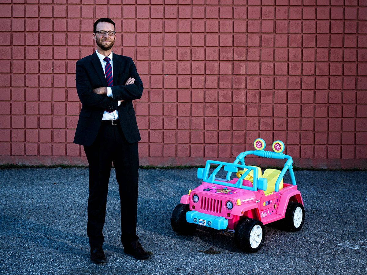 picture of suited man standing next to a toy pink jeep